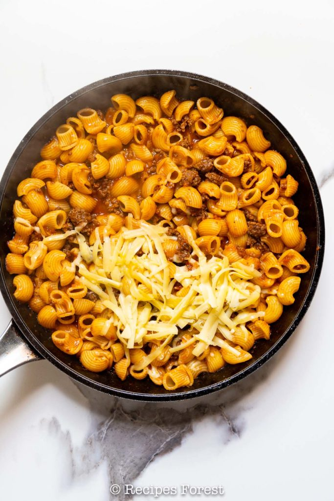 Then you can add in your cooked pasta along with some shredded cheddar cheese and mix everything very gently!